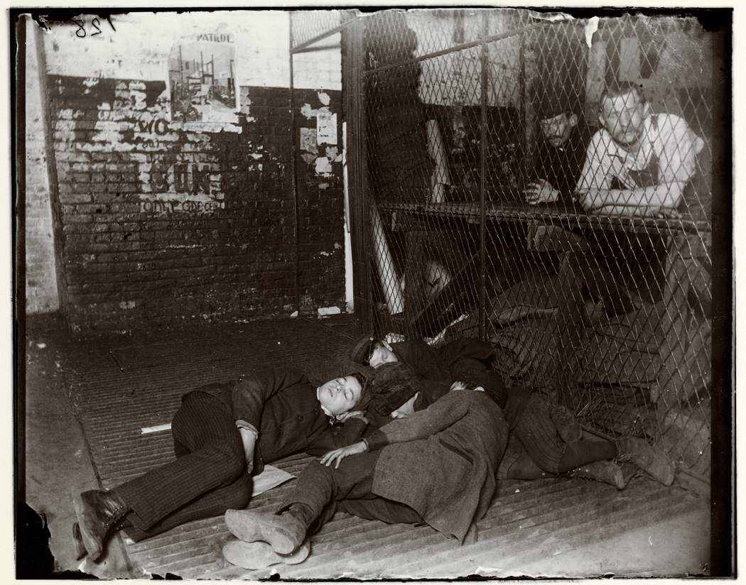 """""""Newsboys Sleeping in the Offices of the New York Sun, 1891-1892"""". Foto di  Jacob Riis.  Museum of the City of New York. Dono di Roger William Riis"""