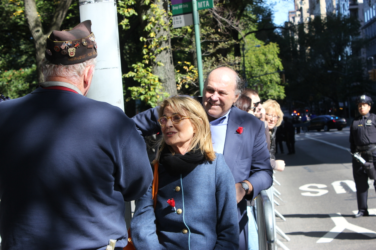 """Madeline and Bill buying Italian flags for the parade: """"We used to see the Columbus Day Parade every year when we lived here. Now we live in Boston and our children and grandchildren are on one of the floats so we're excited for it. And we also lived in Italy for two years."""""""