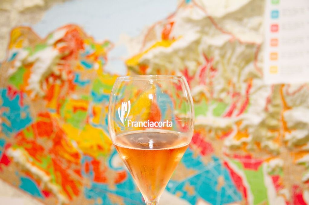 A Glass of Franciacorta Sparkling Rosé with Franciacorta. Topographic Map Behind It. Photo Credit Meghan Schaetzle