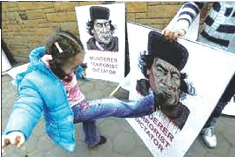 Nella foto una bambina libica prende a calci un manifesto con la foto di Gheddafi