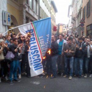 Manifestanti a Brescia bruciano una bandiera del Pdl