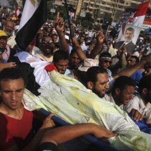 Egiziani sostenitori del defenestrato presidente Morsi, si disperano per la morte di 51 manifestanti uccisi dai militari l'8 luglio (Foto Reuters, Khaled Abdullah)