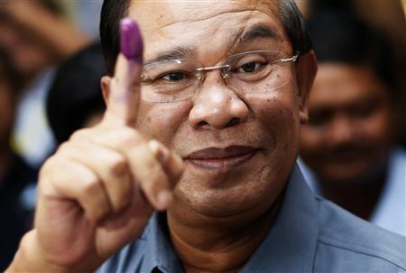Il premier cambigiano Hun Sen mostra il dito dopo aver votato