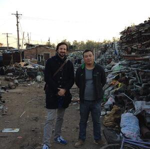 Carlo Ferri con un lavoratore migrante in un magazzino di rifiuti. Foto di Tao Dongyan