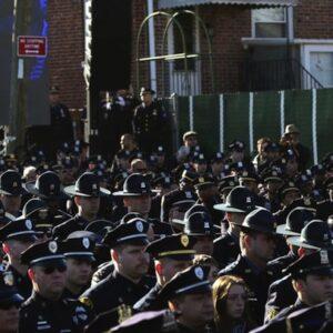 I poliziotti del NYPD voltano le spalle mentre il sindaco Bill De Blasio pronuncia il discorso ai funerali dell'agente Rafael Ramos (Foto Reuters)