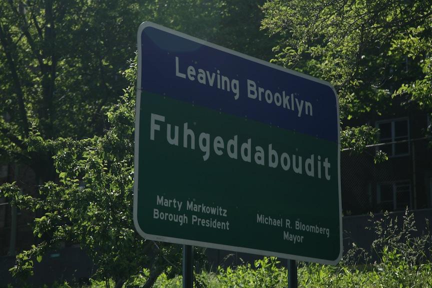 Il cartello stradale al confine tra Brooklyn e Queens sulla strada per l'aereoporto JFK: il cartello messo dal comune di NY, pensando di essere divertente, in realtà tocca un tasto per alcuni dolente dell'esperienza degli immigrati italiani in America