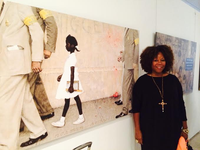 Ruby Bridges poses next to Norman Rockwell's painting The Problem We All Have (1964)